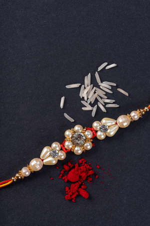 Raksha Bandhan : Rakhi with rice grains and kumkum on black background, Traditional Indian wrist band which is a symbol of love between Brothers and Sisters.