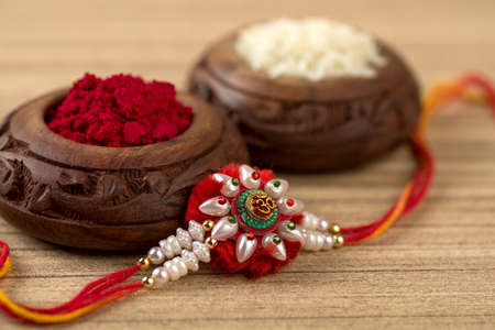 Indian festival: Raksha Bandhan background with an elegant Rakhi, Rice Grains and Kumkum. A traditional Indian wrist band which is a symbol of love between Brothers and Sisters.