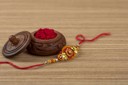 Indian festival: Raksha Bandhan background with an elegant Rakhi, Rice Grains and Kumkum. A traditional Indian wrist band which is a symbol of love between Brothers and Sisters. Stock Photo