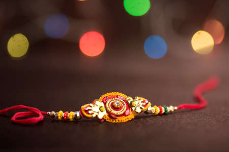 Raksha Bandhan background with an elegant Rakhi. A traditional Indian wrist band which is a symbol of love between Brothers and Sisters. Stock Photo