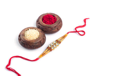 Raksha Bandhan background with an elegant Rakhi, Rice Grains and Kumkum on a white background. A traditional Indian wrist band which is a symbol of love between Brothers and Sisters.