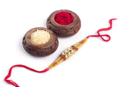 Raksha Bandhan background with an elegant Rakhi, Rice Grains and Kumkum on a white background. A traditional Indian wrist band which is a symbol of love between Brothers and Sisters. Stock Photo