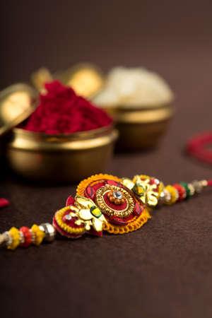 Raksha Bandhan background with an elegant Rakhi, Rice Grains and Kumkum.