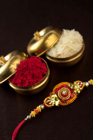 Raksha Bandhan background with an elegant Rakhi, Rice Grains and Kumkum. A traditional Indian wrist band which is a symbol of love between Brothers and Sisters. Imagens