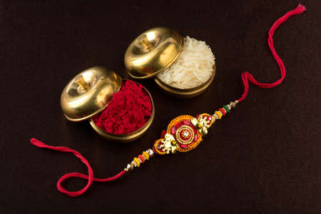 Raksha Bandhan background with an elegant Rakhi, Rice Grains and Kumkum. A traditional Indian wrist band which is a symbol of love between Brothers and Sisters. Stock Photo