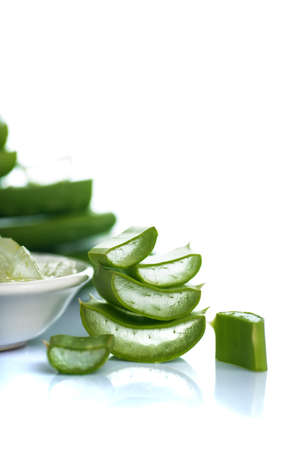Slices of Aloe Vera leave and Aloe Vera gel in a bowl on a white background. Aloe Vera is a very useful herbal medicine for skin care and hair care. 스톡 콘텐츠