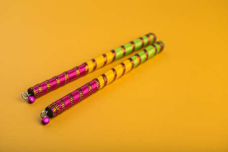 Dandiya sticks on a yellow background. Raas Garba or Dandiya Raas is the traditional folk dance form the state of Gujarat & Rajasthan in India. Stock Photo