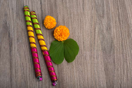 Indian Festival Dussehra and Navratri, showing golden leaf (Bauhinia racemosa) and marigold flowers with Dandiya sticks on a wooden background Stock Photo