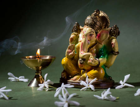 Hindu God Ganesha. Ganesha Idol. A colorful statue of Ganesha Idol on dark background. space for text or headline.
