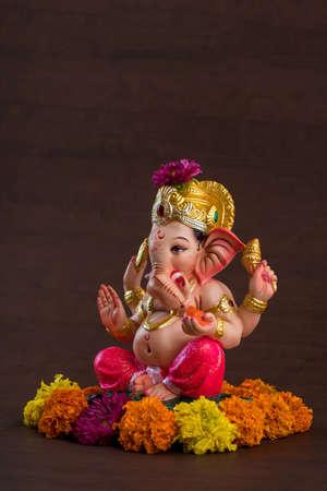 Hindu God Ganesha. Ganesha Idol on dark wooden background.