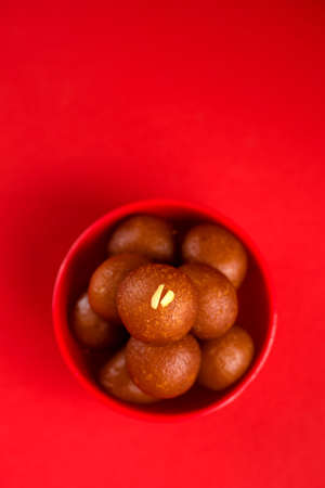 Gulab Jamun in red bowl on red background. Indian Dessert or Sweet Dish. Stock Photo