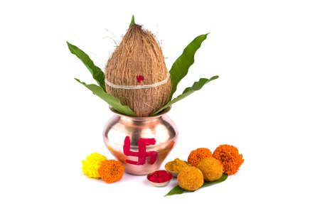 Copper Kalash with coconut, mango leaf, Haldi, kumkum and sweets with marigold flower decoration on a white background. Essential in Hindu puja. Stock Photo