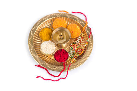 Indian Festival: Rakhi with rice grains, kumkum, sweets and diya on plate with an elegant Rakhi. A traditional Indian wrist band which is a symbol of love between Brothers and Sisters Stock Photo