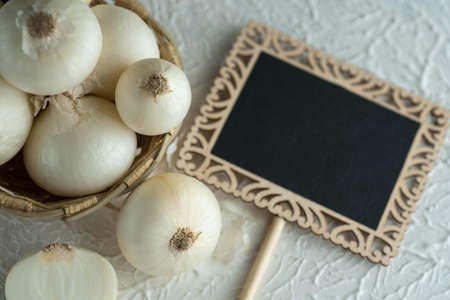 Onions in a wooden bowl with small black board on textured background. Food Ingredients.