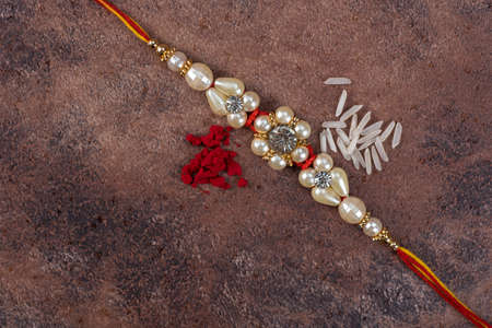 Raksha Bandhan : Rakhi with rice grains and kumkum on stone background, Traditional Indian wrist band which is a symbol of love between Brothers and Sisters. Imagens