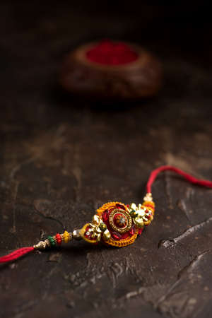 Raksha Bandhan background with an elegant Rakhi, Rice Grains and Kumkum. A traditional Indian wrist band which is a symbol of love between Brothers and Sisters.