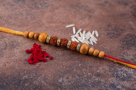 Raksha Bandhan : Rakhi with rice grains and kumkum on stone background, Traditional Indian wrist band which is a symbol of love between Brothers and Sisters.