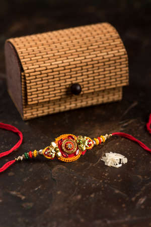 Raksha Bandhan background with an elegant Rakhi, Rice Grains, Kumkum and gift box. A traditional Indian wrist band which is a symbol of love between Brothers and Sisters. Banco de Imagens