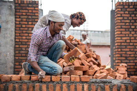 AMRAVATI, MAHARASHTRA - AUGUST 28, 2018: Construction workers working at a development site. Editorial