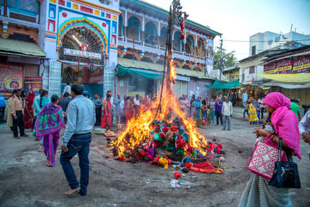 AMRAVATI, MAHARASHTRA, INDIA, MARCH - 1, 2018: unidentified people celebrating Holika Dahan by worshiping of wood logs or coconut. also known as the festival of colors Holi or the festival of sharing