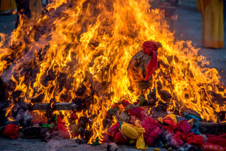 Celebrating Holika Dahan by worshiping and setting fire of wood logs or coconut. also known as the festival of colors Holi or the festival of sharing.