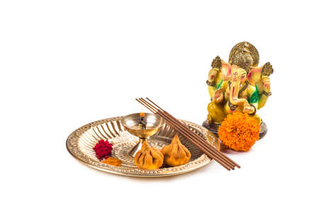 Hindu God Ganesha. Statue of Lord Ganesha. Worship (Pooja) arrangement on white background.