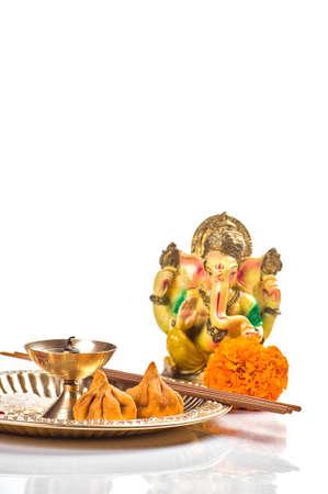 Hindu God Ganesha. Statue of Lord Ganesha. Worship (Pooja) arrangement on white background.