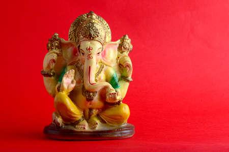 Hindu God Ganesha. Ganesha Idol on red Background.