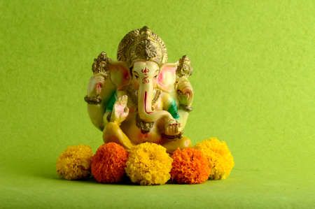 Hindu God Ganesha. Ganesha Idol on Green Background