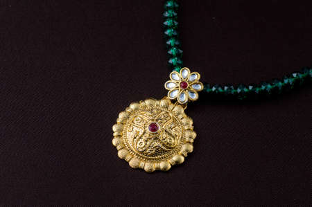 Indian Traditional Jewellery, close up of pendent on dark background Фото со стока