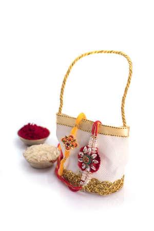 Raakhi and a gift for the sister given by brother on the occasion of Raksha Bandhan. Indian festival Raksha Bandhan background with an elegant Rakhi.
