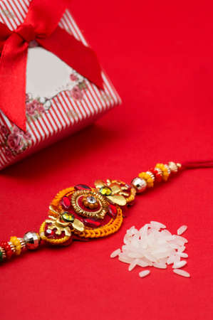 Raakhi and a gift for the sister given by brother on the occasion of Raksha Bandhan. Indian festival Raksha Bandhan background with an elegant Rakhi on red background.