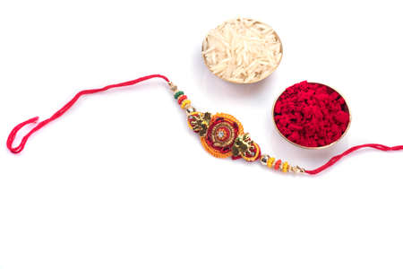 Indian festival: Raksha Bandhan background with an elegant Rakhi on a white background. A traditional Indian wrist band which is a symbol of love between Brothers and Sisters