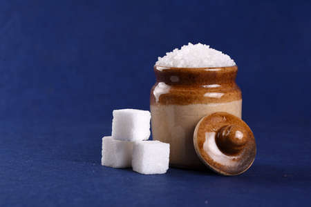 Sugar. white granulated sugar and refined sugar on a blue background