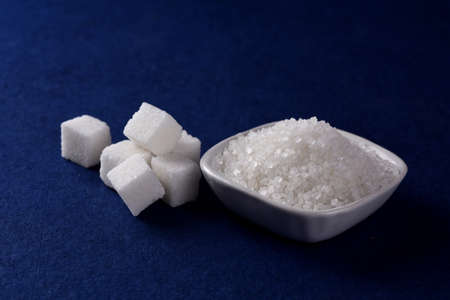 Sugar Cubes with Sugar in white plate on blue background
