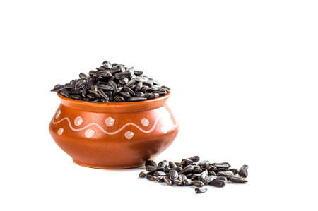 Sunflower Seeds in clay pot on white background. Helianthus annuus.