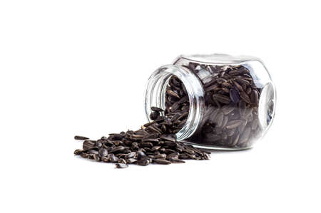 Sunflower Seeds in glass pot on white background. Helianthus annuus.