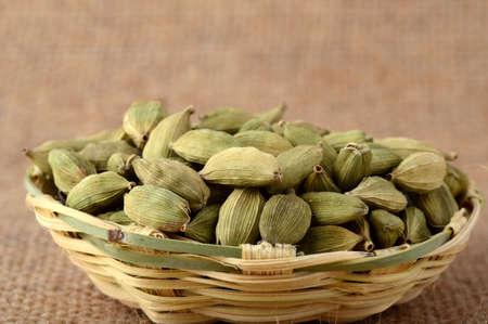 Green Cardamom pods in bamboo basket on sack cloth Stock fotó
