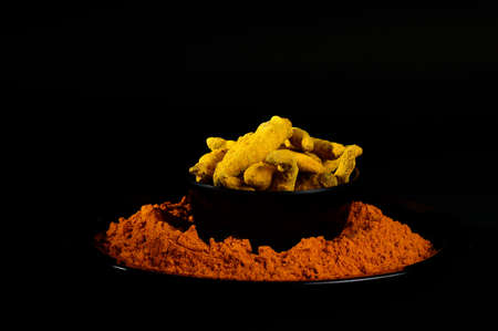 Turmeric powder and roots or barks on black background