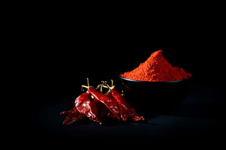 poudre froide dans un bol noir avec des piments rouges frais et séchés sur fond noir