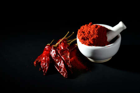 Red Chili Pepper powder in pestle with mortar and Red Chili Peppers on black background Banque d'images