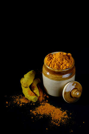 Turmeric powder in clay pot with roots or barks on black background