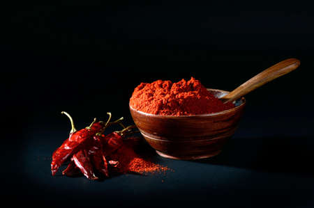 chilly powder in wooden bowl with red chilly, dried chillies on black background