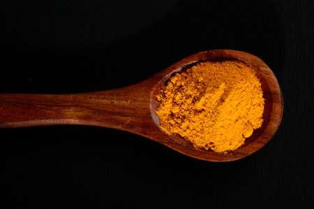 Turmeric powder in spoon on black background