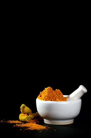 Turmeric powder in mortar with pestle and roots or barks on black background