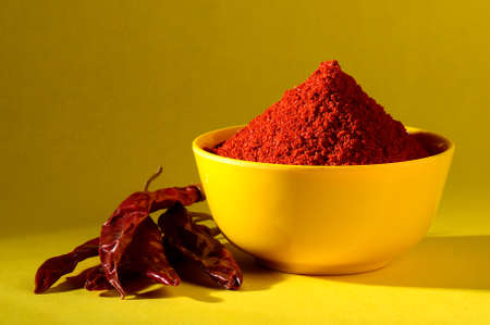 chili powder in yellow bowl on yellow background. Red chilly pepper