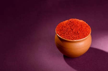 Red Chili Pepper powder in clay pot on dark background
