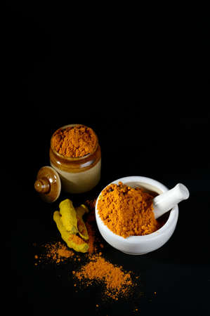 Turmeric powder in mortar with pestle and roots with clay pot on black background