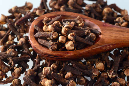 Cloves (spice) and wooden spoon close-up food background. Isolated on white background Standard-Bild