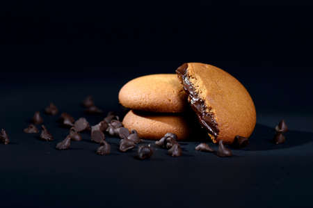 Biscuits filled with chocolate cream. Chocolate cream cookies. brown chocolate biscuits with cream filling on black background. Reklamní fotografie